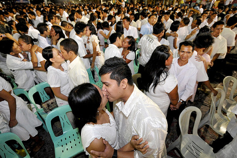Newly-wed couples embrace at a mass Vale